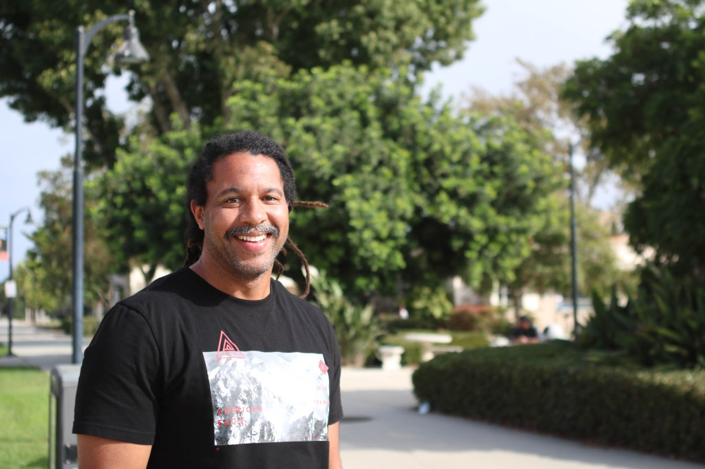 Photo of John Ruff, a person standing outside on the Ventura College campus with trees in the background.